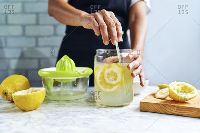 Hands of a womanstirringfresh lemonade