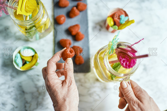 Hands of woman holding single raspberry and pitcher with homemade lemonade