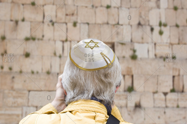 Senior man with kippa in front of a wailing wall