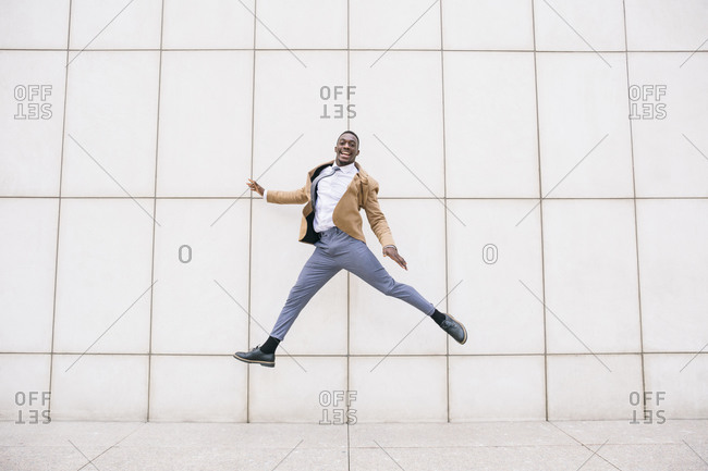 Young businessman jumping in front of a wall