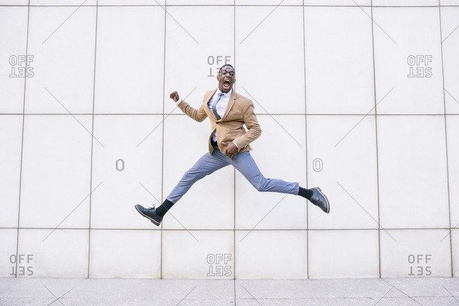 Young businessman jumping and shouting in front of a wall
