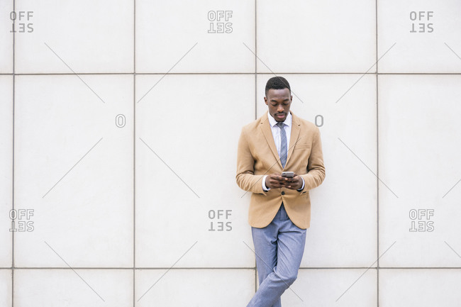 Young businessman leaning against a wall using smartphone