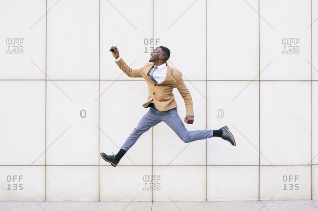 Young businessman jumping and taking a selfie in front of a wall