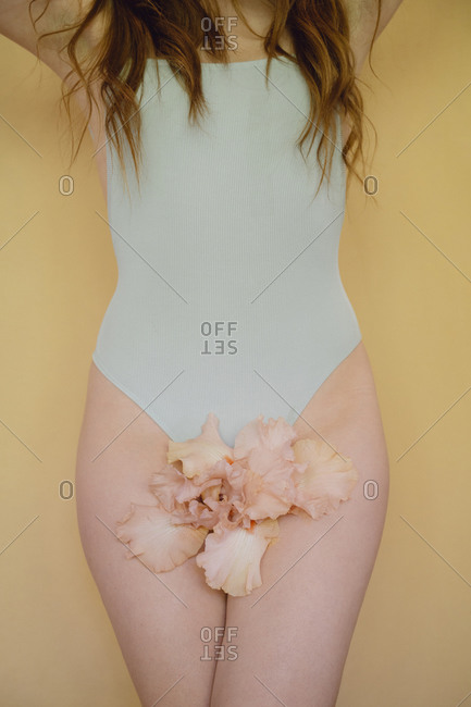 Young woman with pink flower wearing pastel blue swimming suit