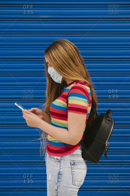Young woman with protective mask and backpack looking at cell phone in front of blue background