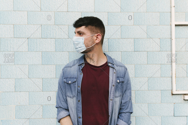 Man with protective mask in front of blue tiled wall
