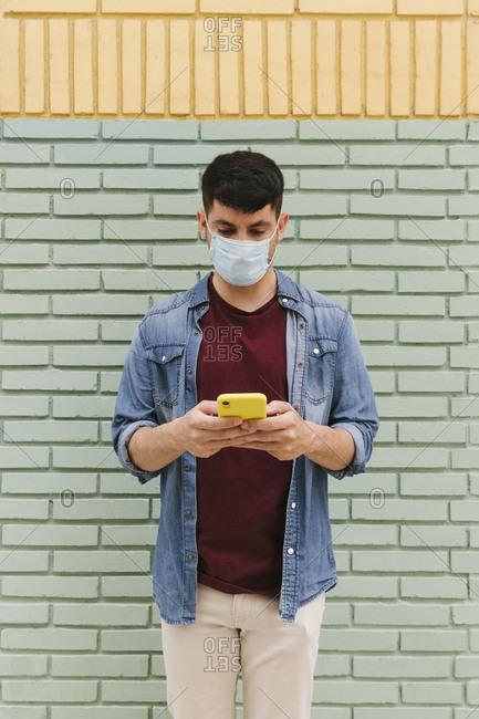 Man with protective mask using cell phone outdoors