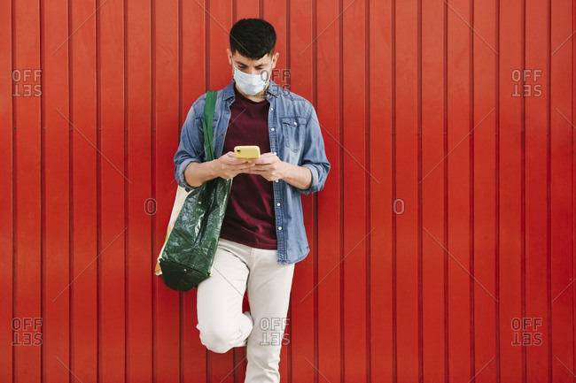 Man with protective mask and shopping bag looking at cell phone in front of red background