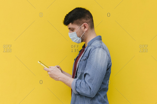 Man with protective mask looking at cell phone in front of yellow background
