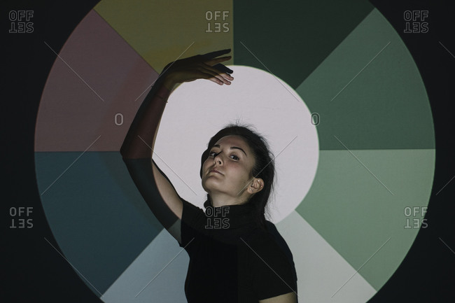 Young woman moving in front of color circle