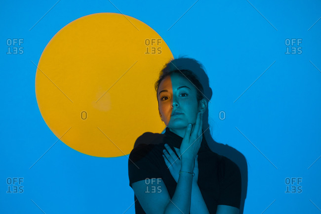 Young woman moving in blue light in front of yellow circle
