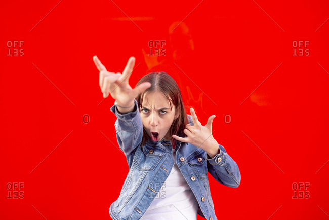 Portrait of teenage girl showing Rock And Roll Sign against red background