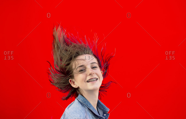 Portrait of smiling teenage girl with braces and blowing hair against red background