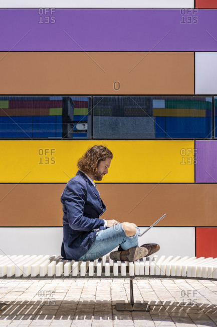 Male professional using laptop while sitting on bench with cross-legged by colorful wall
