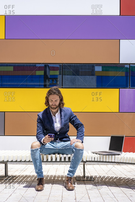 Young male entrepreneur using smart phone while sitting on bench against colorful wall during sunny day