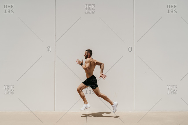 Bare-chested male athlete running along a wall