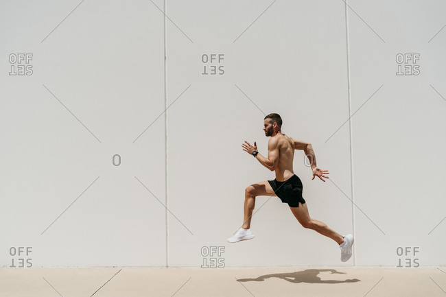 Bare-chested male athlete jumping at a wall