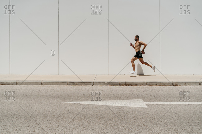 Bare-chested male athlete running on pavement with arrow sign on the road
