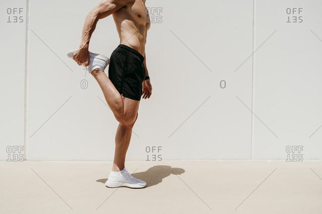 Bare-chested male athlete stretching in sunshine