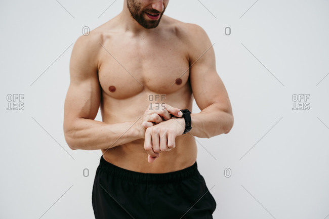 Bare-chested male athlete checking smartwatch