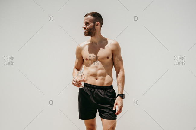 Bare-chested male athlete holding a bottle of water