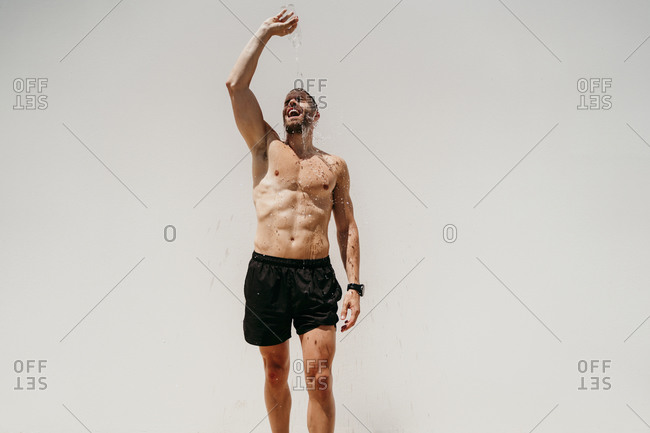 Bare-chested male athlete pouring water over his body