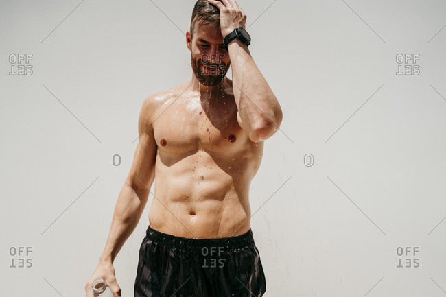 Bare-chested male athlete refreshing with water