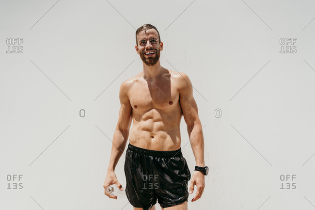 Bare-chested male athlete standing alone