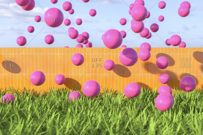 Pink balls flying over wall on a summer day