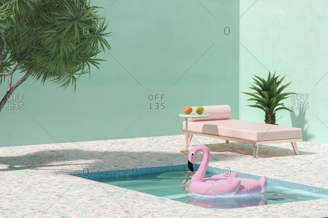 Pink toy flamingo floating on swimming pool next to sunbed and palm trees