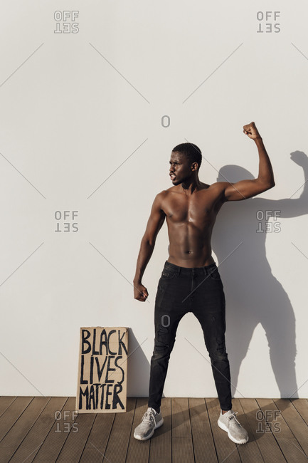Black man raising fist with Black Lives Matter sign leaning on wall