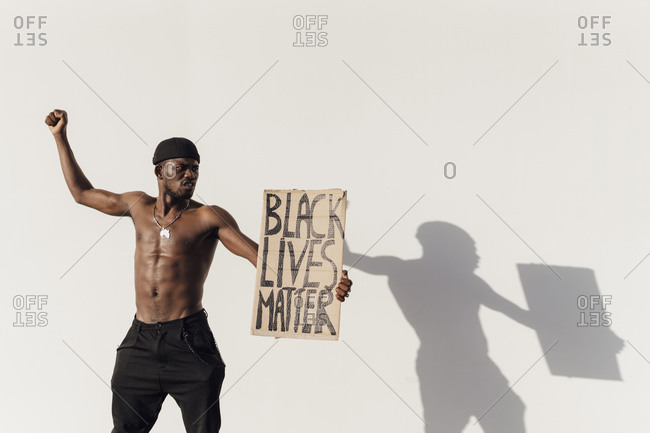 Black man raising fist- holding Black Lives Matter sign