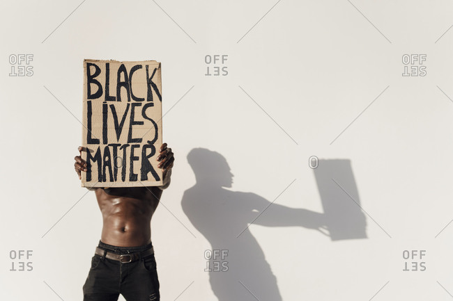 Man holding Black Lives Matter sign in front of his face