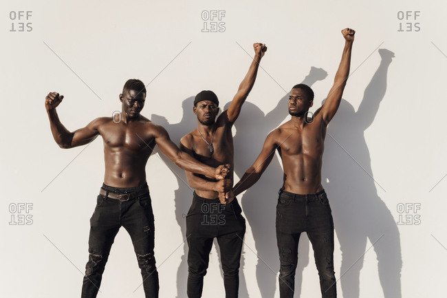 Three men raising fists in protest- standing against white wall