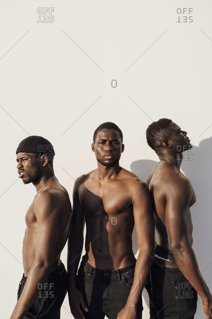 Three black men with bare chest standing in front of white wall