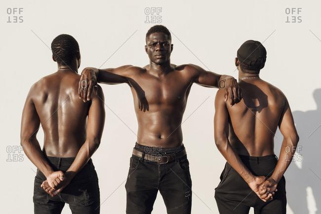 Black man leaning on friends- crossing hands behind their backs