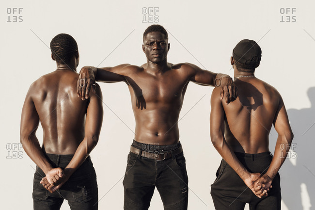 Black man leaning on friends- crossing hands behind their backs