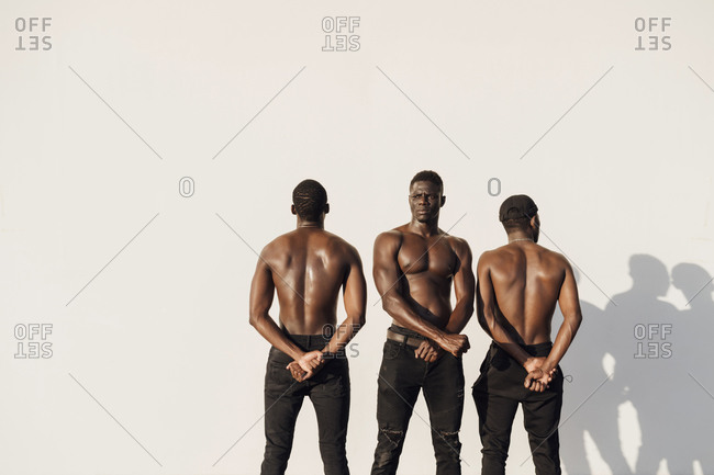 Three man crossing hands in protest- standing against white wall