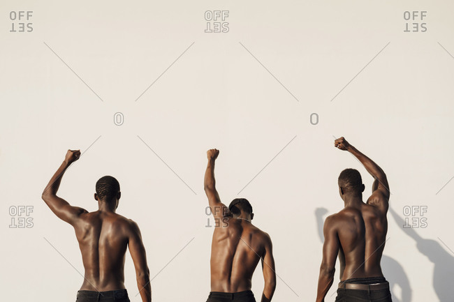 Three men raising fists in protest- standing against white wall- rear view