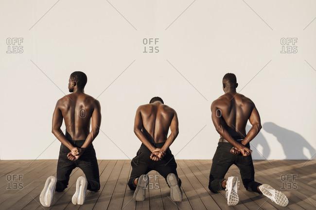 Three man crossing hands behind their backs- kneeling on planks