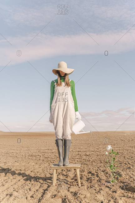 Woman standing on stool- watering flower on barren field