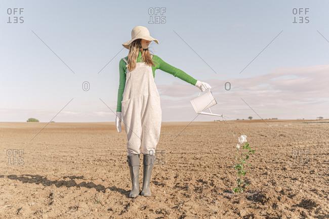 Woman standing on barren field- watering flower