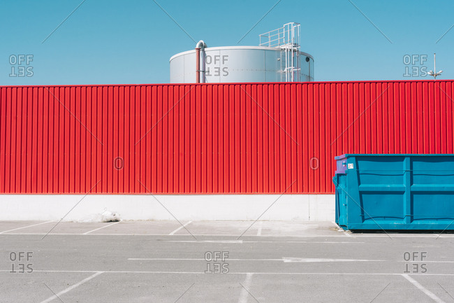 Blue container in front of red wall in industrial setting