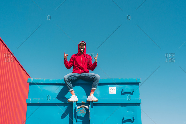 Young man wearing red hoodie- sitting on edge of blue container- making sign of the horns