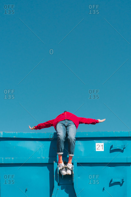 Young man relaxing on blue container- leaning backwards over edge