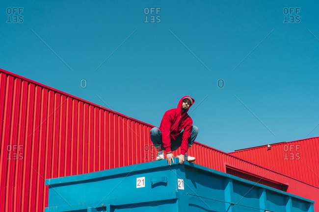 Young man wearing red hooded jacket crouching on edge of container in front of red wall