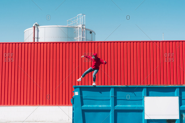 Young man wearing red hooded jacket balancing on edge of container in front of red wall in industrial setting