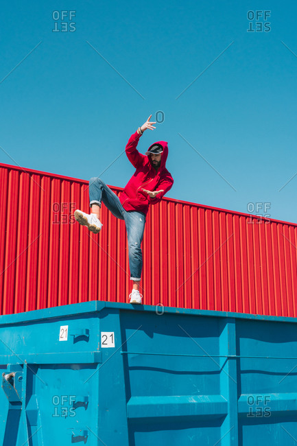 Young man wearing red hooded jacket balancing on edge of container in front of red wall