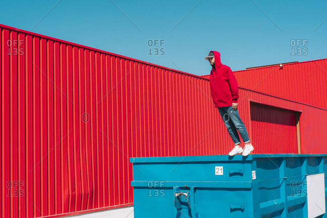 Young man wearing red hooded jacket standing on edge of container in front of red wall