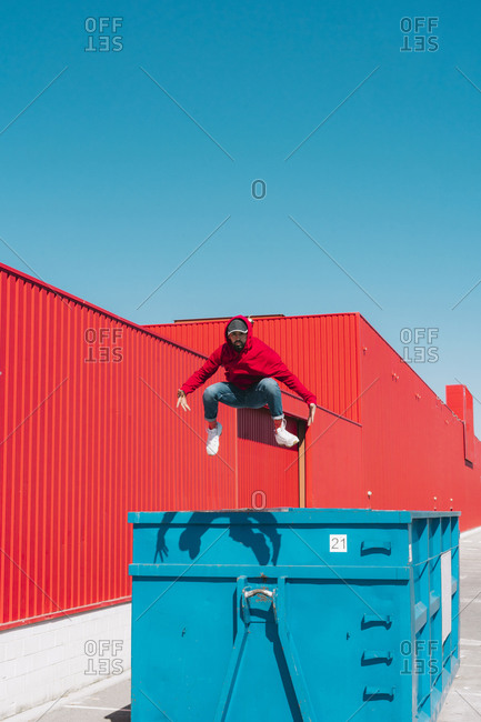 Young man wearing red hooded jacket jumping from edge of container in front of red wall